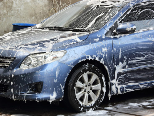 washing a blue car with a foam and water